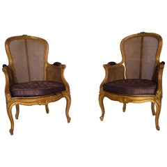 A pair of French carved and gilt caned armchairs, 19th Century