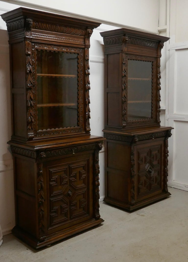 A pair of French carved Gothic oak bookcases  The upper section of the Bookcases have a glazed door enclosing 2 adjustable book shelves, these have an attractive carved front edge.  The Tops have a large carved cornice and there is carving on the