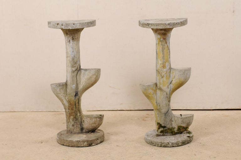 A French pair of garden foliage inspired, tiered sculptural shelves from the mid-20th century. This vintage pair of cast-stone garden or patio decorations from France each features a rounded base which supports a plant shaped sculpture, topped with
