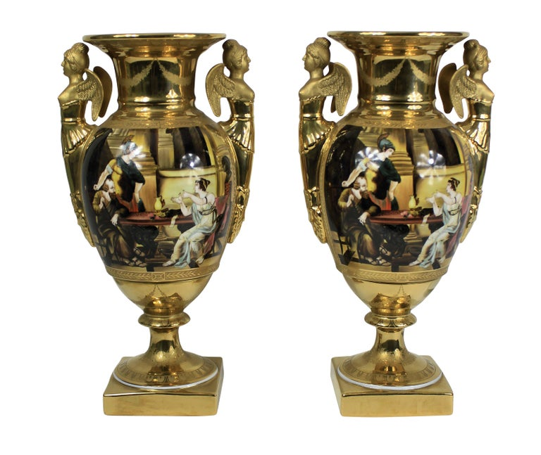 A pair of French hand painted ground gold porcelain vases, depicting Classical scenes, with an armorial crest and crown.