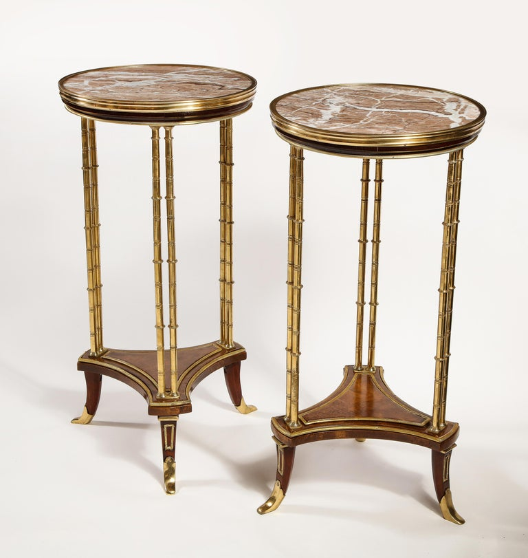 A pair of French Louis XVI style gilt bronze mounted mahogany marble-top circular form side tables of great workmanship embellished with gilt bronze bamboo legs, triangular center stretcher and further adorned with fine marble tops.