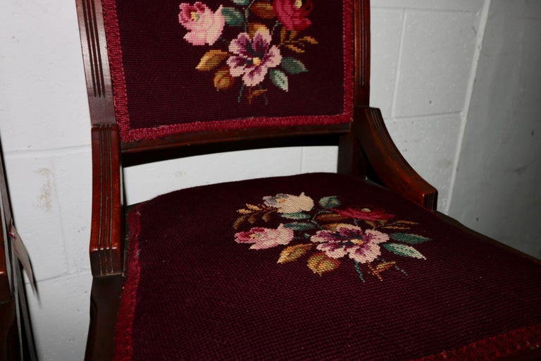 A pair of French mahogany hand carved scroll work crewel embroidered chairs. Elegant floral scroll work accent the top of each chair. Crewel embroidered wool fabric with fantastic colors adorn the seat and back. A pleasant flora. Of the Baroque