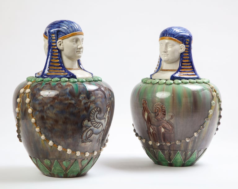 A pair of Egyptian style French majolica vases with pharaoh-head form covers made in the late 19th century. The canopic-form vases are adorned on the mouth-rim with a ring of scarabs and geometric patterns encircling the foot. The body is decorated