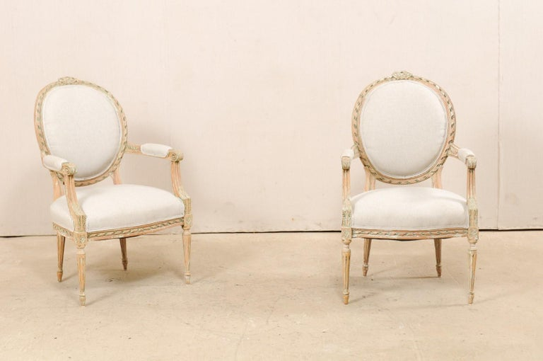A pair of French carved wood and upholstered bergères chairs from the mid-20th century. This vintage pair of armchairs from France each feature oval-shaped upholstered backs with a wood frame accentuated with spiraled ribbon carved trim and pierced