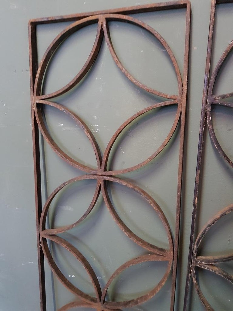 A pair of vintage French wrought iron door grilles decorated with diamonds and circles, both are in good but used condition. Originating from the second half of the 20th century.  The measurements are, Depth 2 cm/ 0.7 inch. Width 31 cm/ 12.2