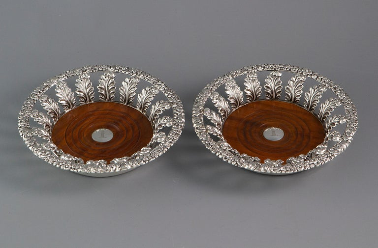 An exceptionally good pair of Georgian silver wine coasters of flared form with cast flowerhead and scrolling foliate rims supported by embossed leaves. Turned fruitwood bases with the central silver button engraved with the crest of a dragon