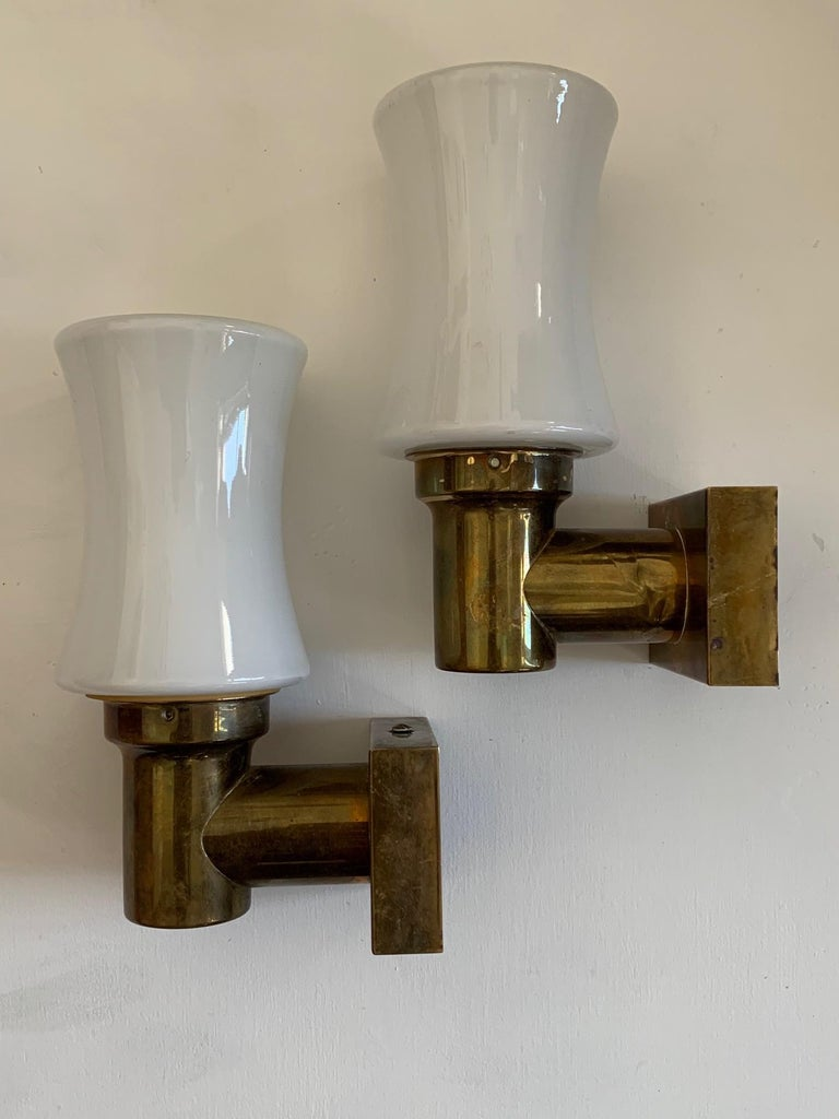A pair of unusual sconces from Germany, circa 1950s. Brass and opaline glass, they can be hung up or down. Small scale, perfect as vanity/bathroom lights or anywhere in the room.