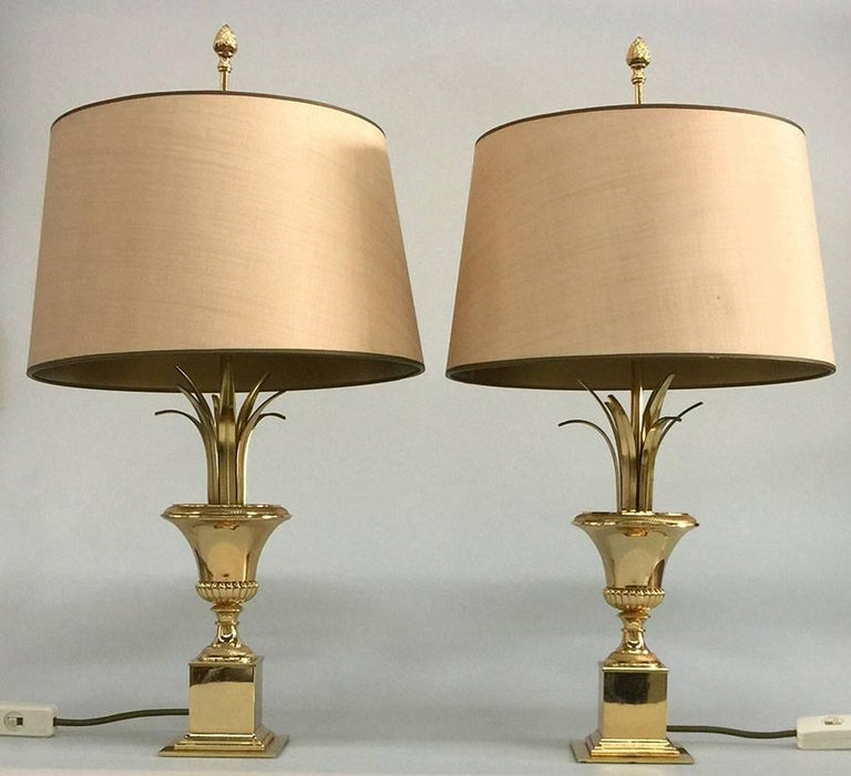 A pair of gilt metal Italian side table lamps, 1970s  In total 56 cm high The shade is 25 cm diagonal The foot is 9 cm square.