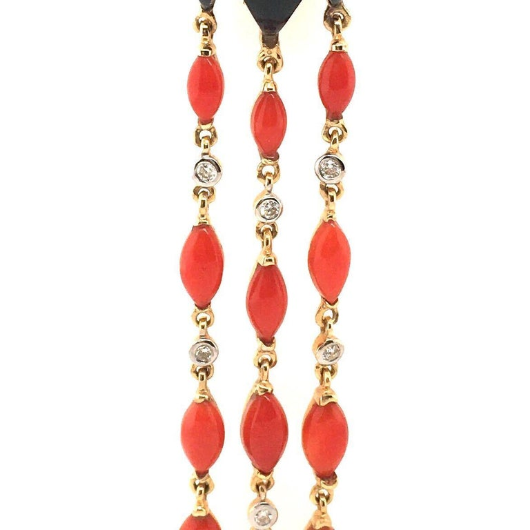 A pair of 18 karat yellow gold, orange-red coral, black onyx and diamond dangling earrings with collapsible posts & omega backs.  Each earring suspends three line pendants, each  set with five coral navettes and two circular cut diamonds, all joined
