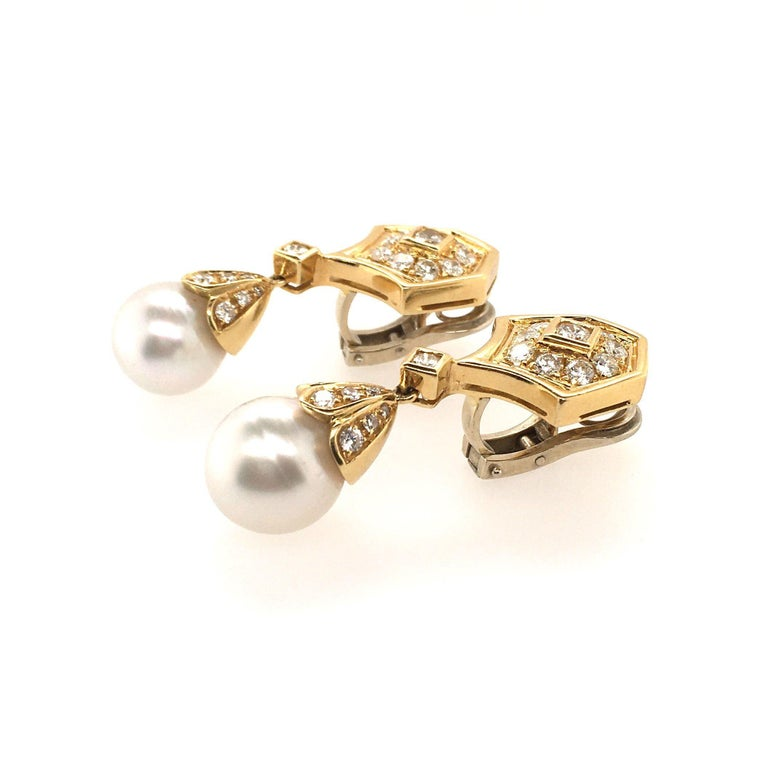A pair of 18 karat yellow gold, diamond and pearl earrings. Designed as a shield shape set with circular cut diamonds, suspending a drop shaped pearl, measuring approximately 12.4 and 12.6mm, from a pave set diamond cap. Forty (40 ) diamonds weigh