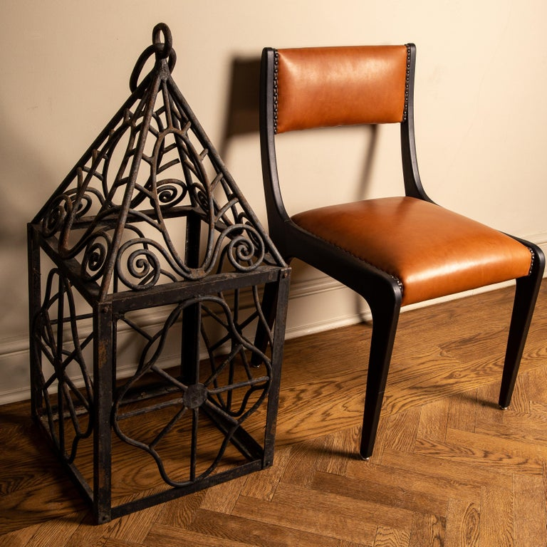 Unusual and elegant pair of heavy hurricane lanterns, fashioned out of solid wrought iron, with ornamental scrolling design. Impressive proportions and superb craftsmanship, featuring distinctive fluid like form/pattern make these a statement in any