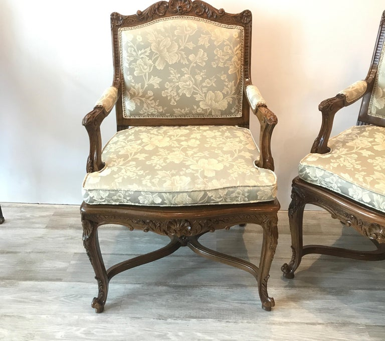 A pair of hand carve walnut framed open armchairs with new fabric. The frames with hand carved detailing all-over with new light sage damask fabric. Beautiful warm dark wood with clean smooth finish.. Measures: 25 wide, 38 high 24 deep 20 seat...