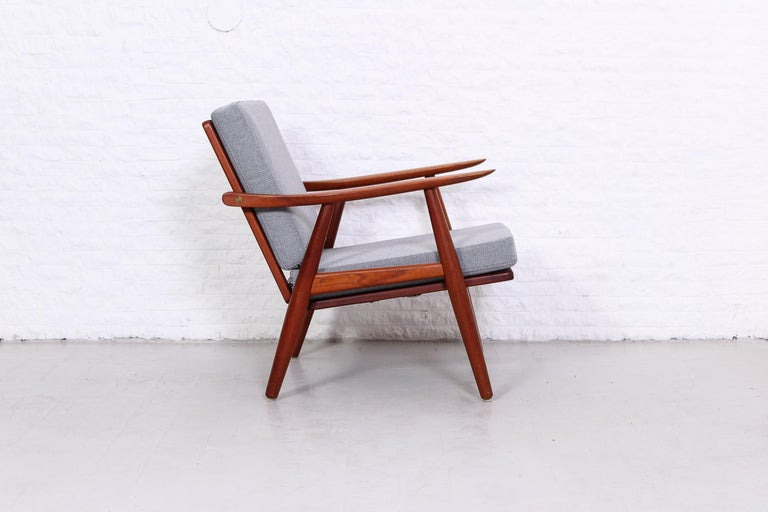 A pair of Hans J Wegner easy chairs, model GE-270. Produced by GETAMA in the late 1950s. Solid teak frame with brass details, new cushions upholstered in a wool fabric and new straps in the seat. Excellent condition.   Two identical chairs