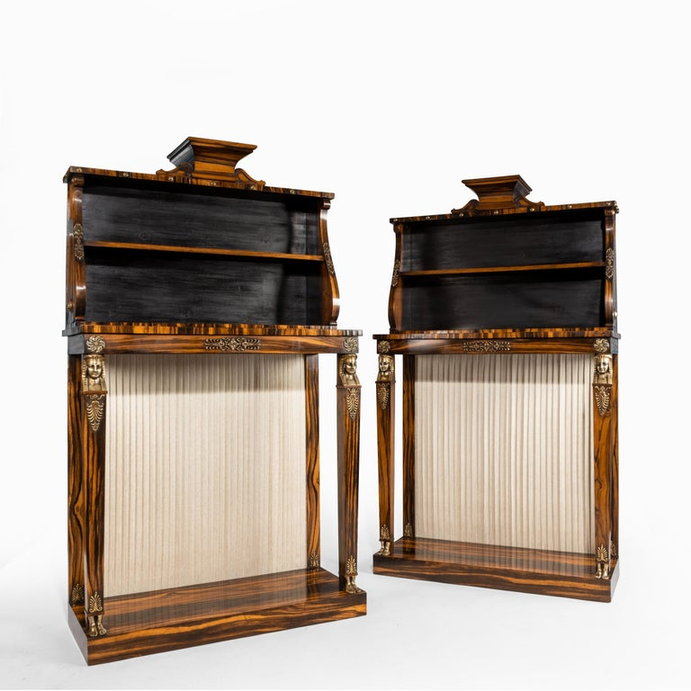A pair of high Regency Coromandel and ormolu bookcase console tables in the style of Thomas Hope, each of rectangular form with two square section pillars in the form of pharaonic terms with bare feet, on a solid plinth, surmounted by two shelves
