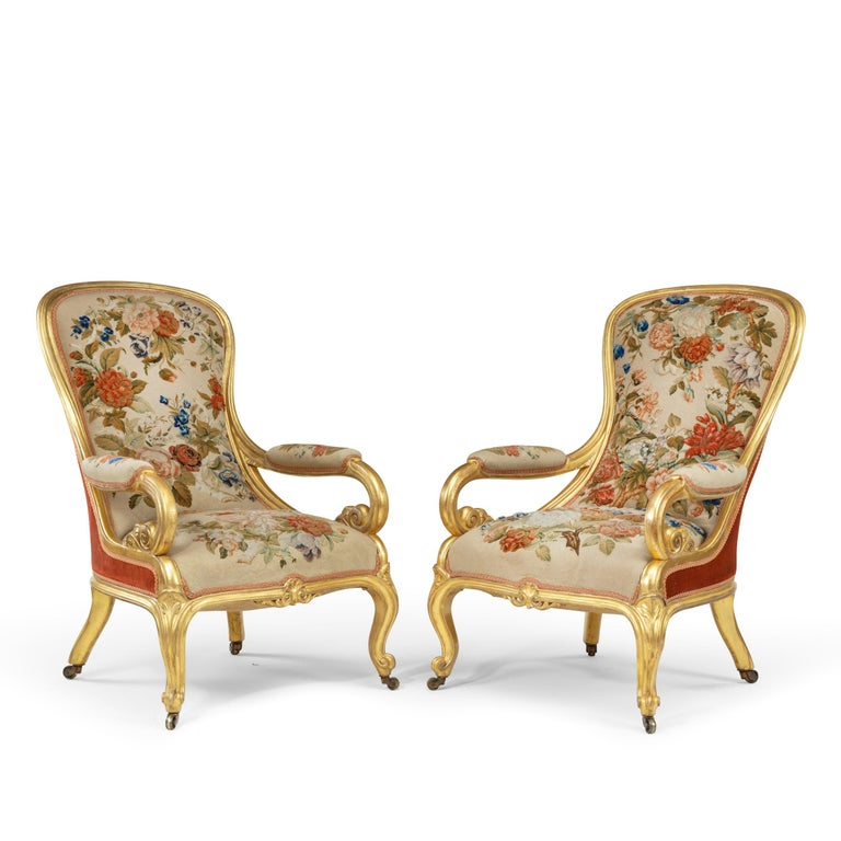A pair of high Victorian giltwood and needlework arm chairs by Gillows, each with a shaped hooped back continuous with the scrolling open arms with half acanthus terminals, the shaped front rail centred on an anthemion, all raised upon carved