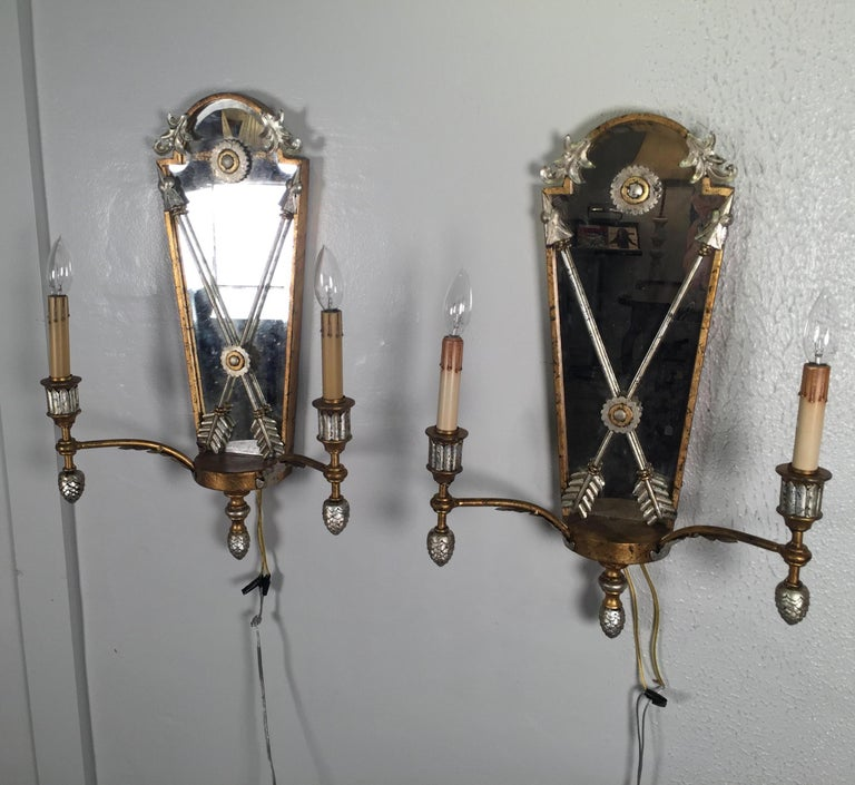 The two light sconces with silver and gold gilt with distressed mirrored backs. The back panels with a neoclassical double crossed swords.