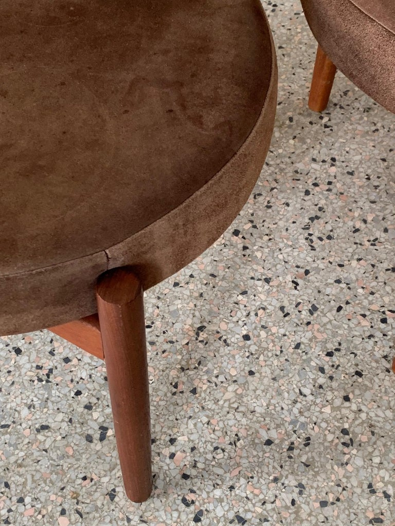 A pair of Classic three-legged stools by Hugo Frandsen for Spottrup, Denmark, circa 1960s. Suede upholstered seats.