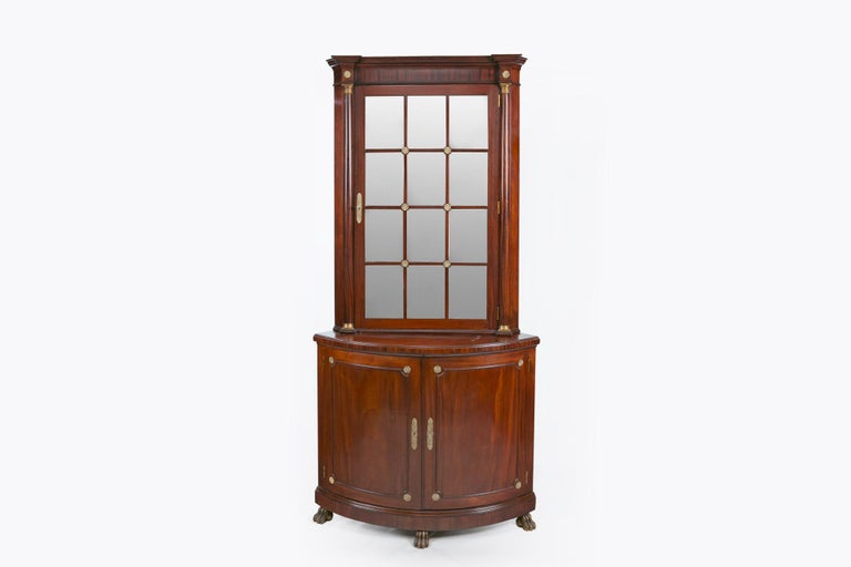 A pair of Irish 19th century mahogany corner cabinets with mirrored panelled doors and brass fittings, above double door demi lune base. Terminating on hairy paw feet.