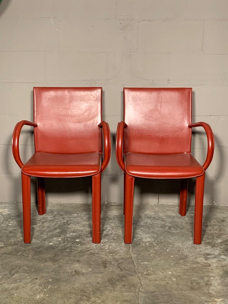 A pair of interesting leather armchairs by Arper, Italy, circa 1980s. Heavy and well made, in the style of Adnet. The color is burgundy.