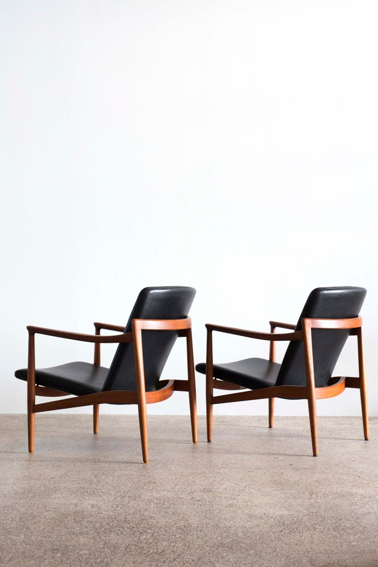 A pair of teak easy chairs designed and executed by Jacob Kjaer, Denmark. Designed 1954 and made in 1962. Black dyed natural leather upholstery, brass fittings and adjustable back.