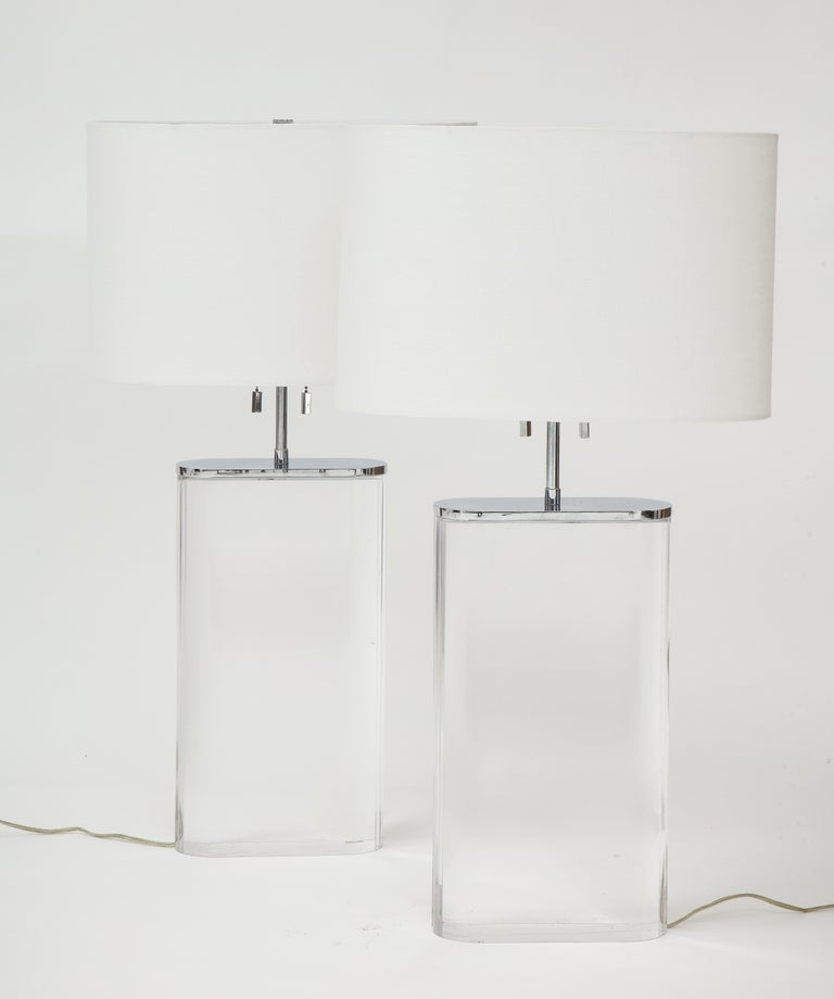"""A large scale pair of Lucite and chrome mounted oblong form table lamps by Karl Springer. Purchased from Karl Springer circa 1982-1984, with new shades. Adjustable height. Lucite base: 16.3/8 H x 9"""" W x 3 ½"""" D To top of shade 29in."""