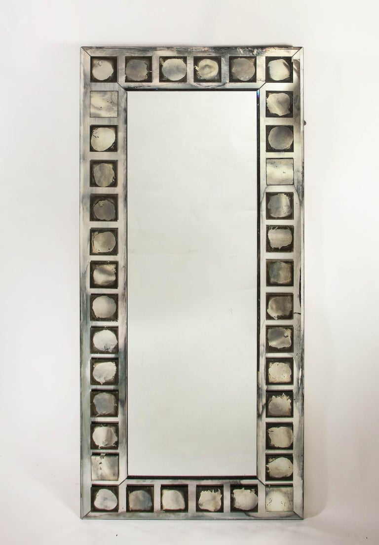 A pair of unique and large antique French Art Deco geometric rectangular form mirrors of unusual design embellished with square shaped antiqued mirrored panels.