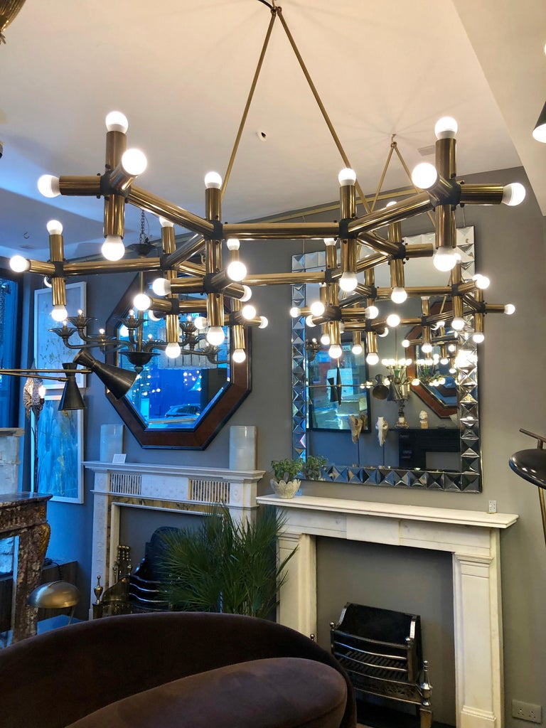 An unusual and very large pair of tubular geometrical chandeliers in brass. Having 54-light fittings in each light. Hung from the ceiling with brass matching hooked rods. Imported from Paris and installed in Mayfair London. Then purchased by us. A