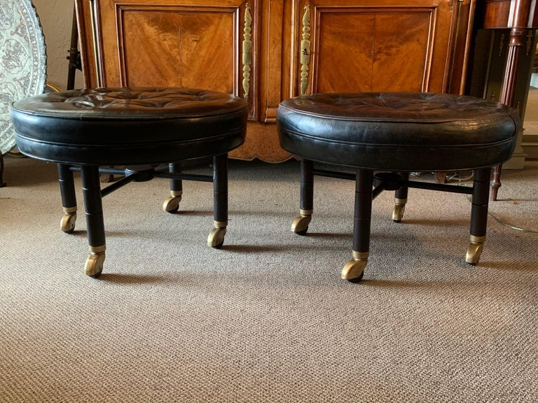 A pair of classic large scale ottomans by Baker on heavy casters. Original black leather tops. Frames restored.