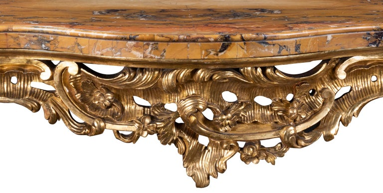 The serpentine fronted marble top with ovolo molded edge over carved rosettes, C scrolls and rocailles, the sides with conforming decoration, each canted cabriole leg headed with foliate scroll to leaf sabot and scroll foot, joined by x- form