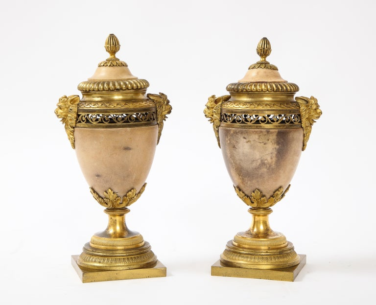 A fabulous pair of Louis XVI Northern European neoclassical ormolu mounted marble potpourris. The body of each is hand-carved from a very fine quality peach-ish-colored marble. Each side is flanked with exceptionally cast, hand-chassed, and