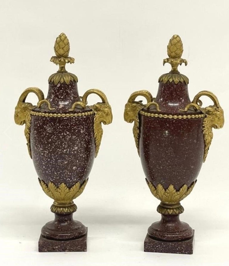 The mounts are similar to those by Gouthière. The one vase having more speckling of white in the porphyry than the other.
