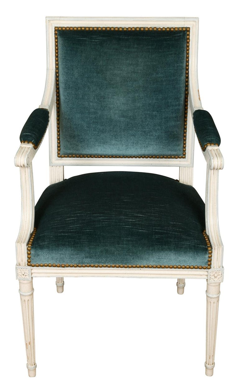 We love these Louis XVI style arm chairs for their clean lines and quiet elegance. These chairs, painted in white with a soft gray accents, feature many details characteristic of the Louis XVI style-- a square back, fluted tapered legs and a carved