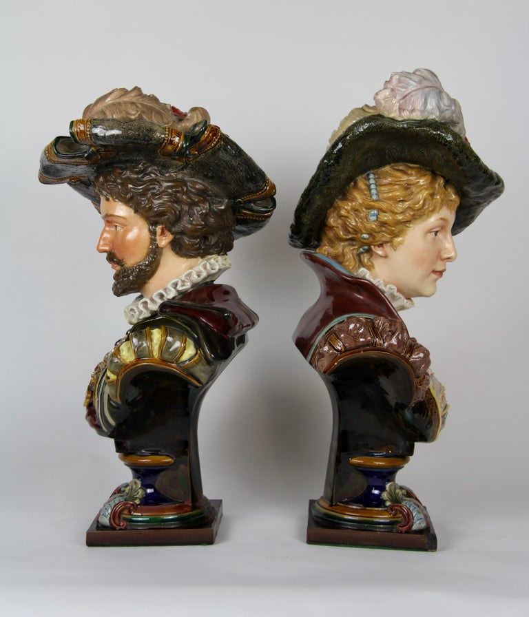 A large pair of Belle Epoque style French Majolica Porcelain Busts of Royals. Each is beautifully hand-painted with extraordinary care and skillful artwork. Both royals are wearing royal attire complete with feathered hats and jewelry, all made of