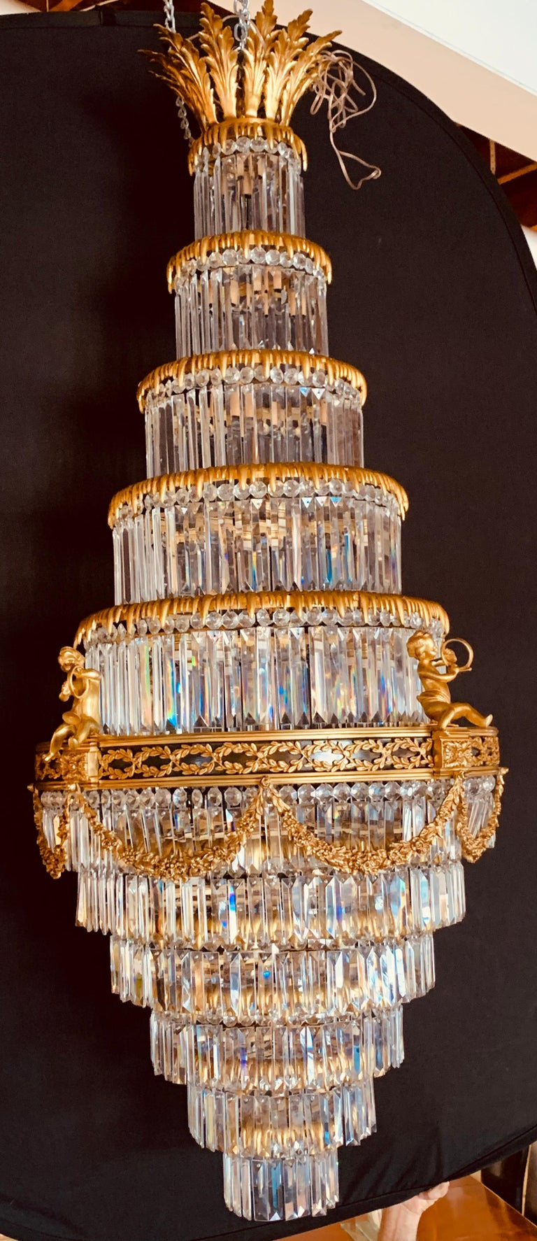 A pair of Louis XVI style gilt bronze & crystal swag form neoclassical chandeliers. stunning beyond words are these one of a kind pair of king crowned lights. each having a Fine cut crystal drapery form of tiers all layered in bronze circular