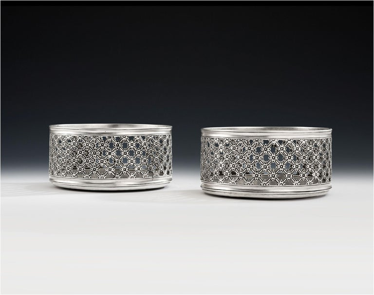 This exceptionally rare and unusual pair of floral trellis work silver based magnum wine coasters were made in London in 1852 by Daniel & Charles Houle. Both pieces are of a large size, with deep sides and plain silver bases. The sides are pierced