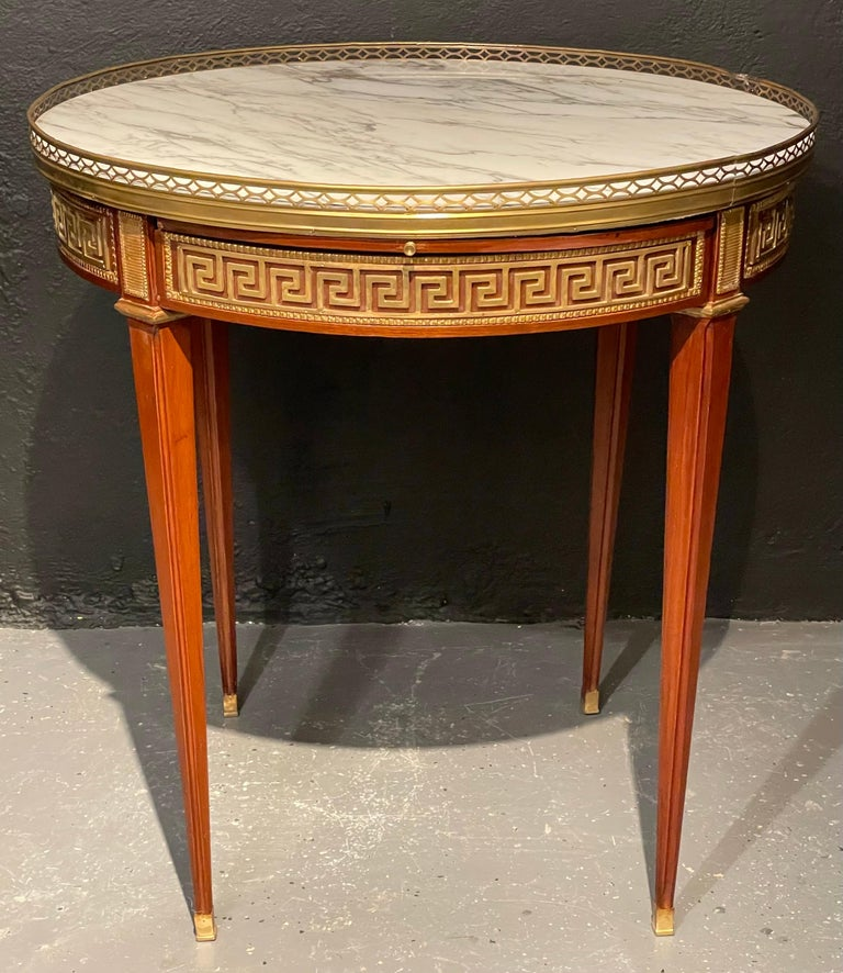 A pair of marble top Greek Key Bouillotte or end tables. Manner of Jansen in mahogany with double drawers and pull-out slides. Each bronze sabot leading to a group of tapering legs terminating in bronze capitals supporting an apron have full Greek
