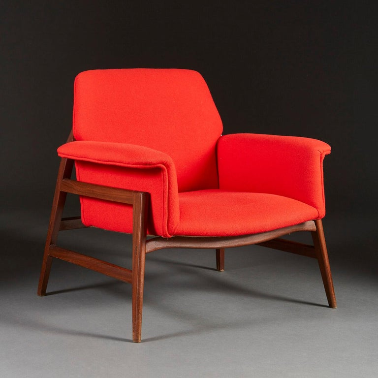 A pair of mid twentieth century Italian armchairs with outswept arms, the seat and back upholstered in a crimson red Danish wool, and supported on a teak wood base with tapering legs.