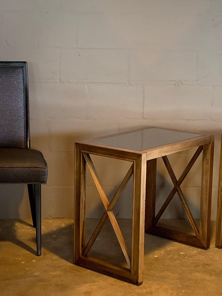 A pair of elegant side tables by James Mont, circa 1950s. Featuring X-shape sides and mirrored tops.