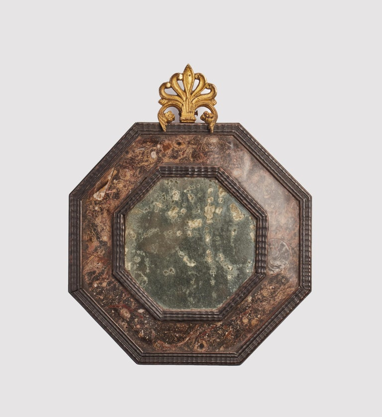A pair of Wunderkammer mirrors, with black wooden octagonal frame, covered with Lumachella stone. Goldgilt brass frieze, Italy, circa 1800.