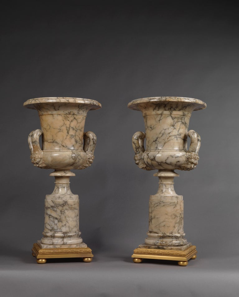 A fine pair of neoclassical style carved alabaster vases with mask handles.