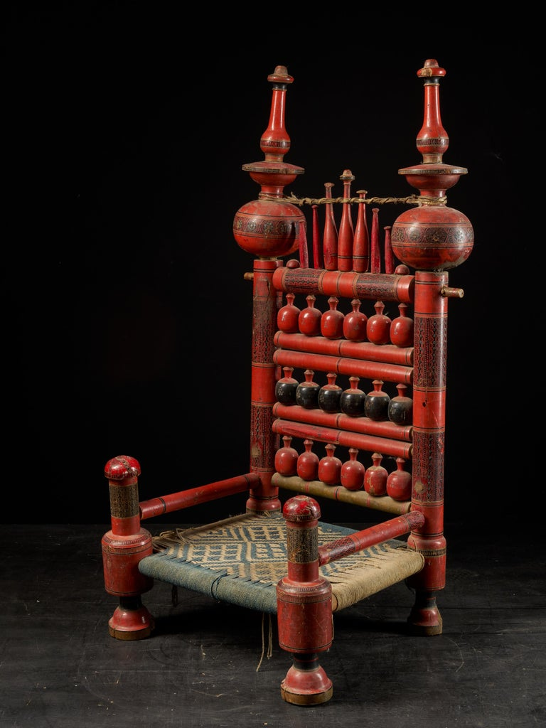 A pair of old Punjabi handcrafted wooden tribal wedding chairs with intricate woven rope seating. The chairs are hand painted in vibrant reds and blacks slightly fading. The minor losses and the wonderful gently worn patina commensurate with its age