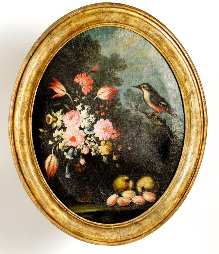A pair of oval still lifes attributed to the early 19th C Milanese School, c 1820. The pair of still life oil paintings depict flowers, pears and a bird perched on a tree branch in a landscape. Ovals are rare because they were more difficult to make