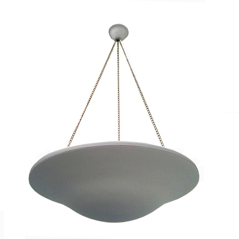A pair of beautiful plaster pendant lights of circular shape, held by three adjustable brass chains.