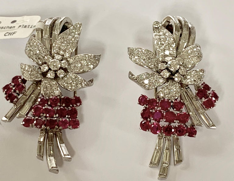 A pair of  Retro platinum clips with rubies and diamonds. The pair of clips have 17 rubies with an approximate total weight of 2.50 carats, 22 baguette diamonds of circa 2.20 ct,  and various European-cut diamonds  and resort diamonds with an
