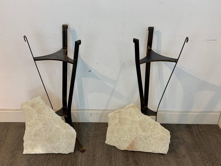 A pair of rock crystal and iron pedestals, each one with a live edge slab of rock crystal / quartz raised on a tripartite, two tiered iron pedestal. Interchangeable slabs, one measuring 16
