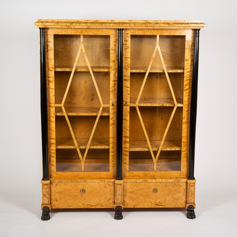 A pair of 2-door glazed satin birch bookcases, with ebonized columns and paw feet, Swedish, circa 1925.  Each with two drawers and adjustable height shelves.   with keys.