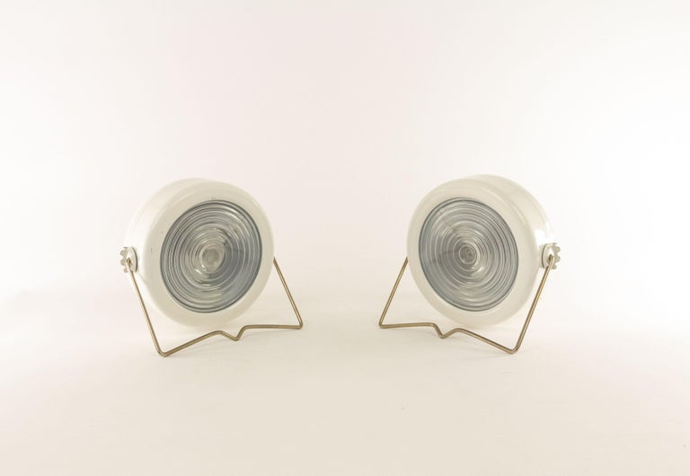 A pair of Sciukolamps designed in 1966 by Achille & Pier Giacomo Castiglioni and produced by the Italian lighting manufacturer Flos.  The lamp consists of a enameled metal body with two gears which allow the bracket to lock into different