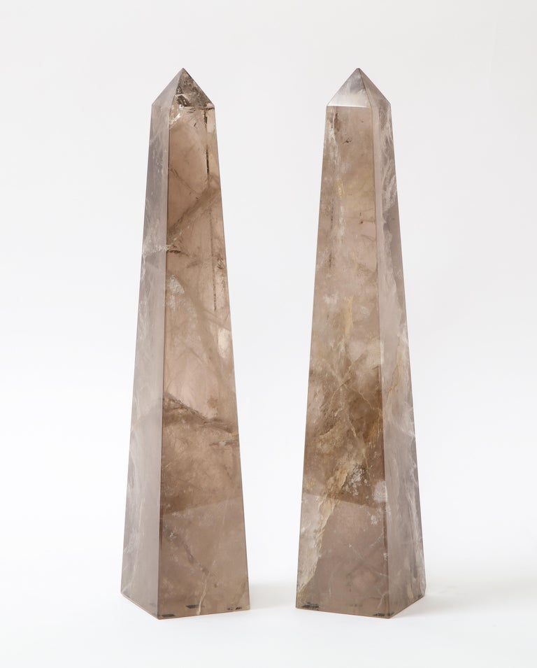 A gorgeous and quite decorative pair of Mid-Century Modern French Smokey rock crystal quartz hand carved and hand-polished obelisks. Each obelisk is made of a natural Smokey rock crystal quartz which has been hand-diamond cut and hand-polished with