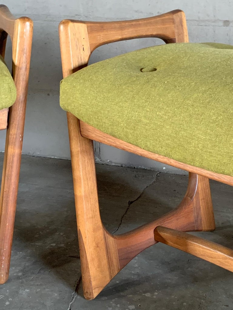 A pair of unusual ottomans by Adrian Pearsall. Walnut frames with upholstered seats. Legs have a characteristic slant.