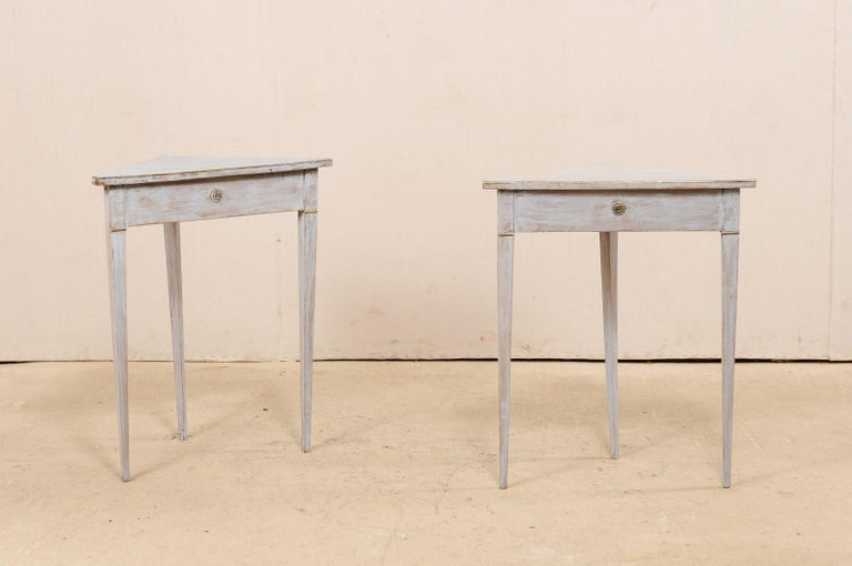 A pair of Swedish painted wooden corner tables from the 19th century. This pair of antique tables from Sweden each have triangular-shaped tops allowing them to be easily used in a corner space. The aprons are nice and clean, each adorned at its